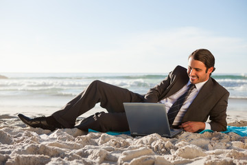 Smiling businessman lying on the side on the beach