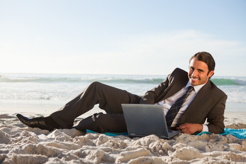 Smiling businessman using a laptop on the beach