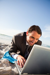 Smiling businessman using his laptop while lying on the beach