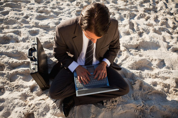 Overhead view of a young businessman sitting cross-legged on the beach