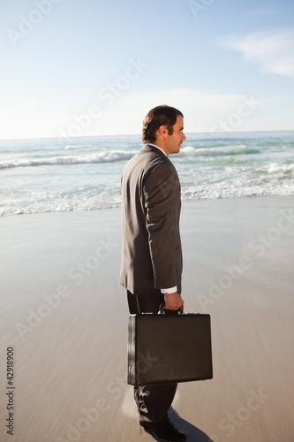 Side view of a businessman looking in front of him while standing on the beach