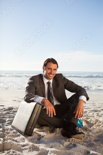 Smiling businessman sitting cross-legged on the beach