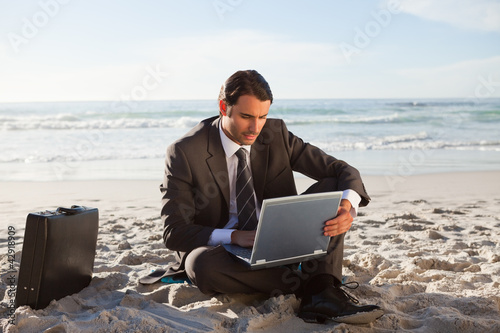 Serious businessman using a laptop while sitting cross-legged