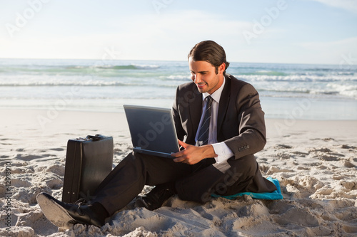 Smiling businessman sitting cross-legged on the beach with a laptop