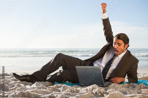 Happy businessman raising his arm in success