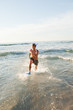 Young happy man running in the water with fins