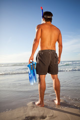 Young attractive man standing on the beach with a snorkel and fins