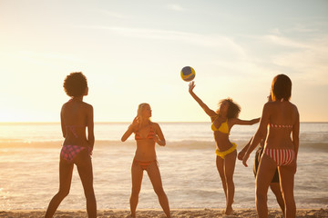 Young women playing with a beach ball in front of the sea