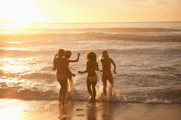 Young women getting in the water at sunset