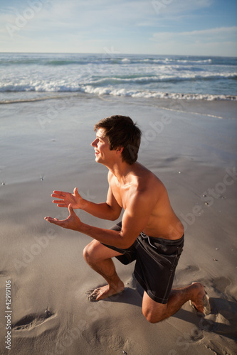 Young attractive man playing on the beach