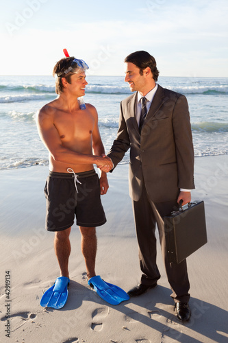 Young men shaking hands on the beach