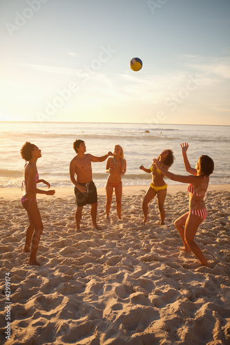 Young people in swimsuits playing with a beach ball