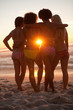 Rear view of young friends holding each other in front of the sunset
