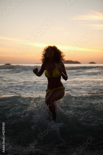 Young attractive woman jumping in the water