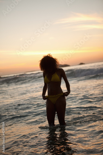 Young woman in a yellow swimsuit standing in the water
