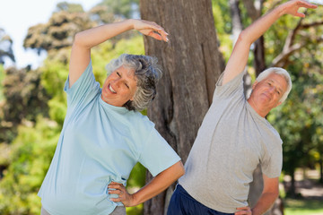 Elderly man and woman are wearing jogging gear and stretching