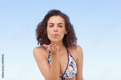 Woman blowing a kiss in front of her