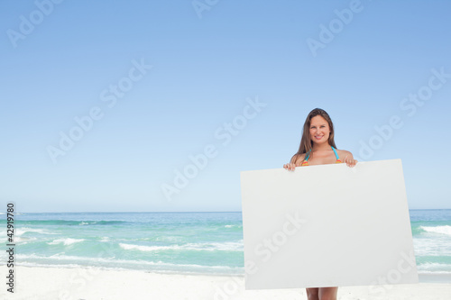 Woman wearing a bikini holding a blank poster in front of her
