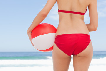 Woman holding a beach ball against her hip