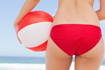 Close-up of a woman holding a beach ball against her hips