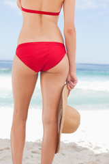 Woman in a red bikini holding a hat
