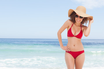 Woman in beachwear smiling while holding the brim of her hat
