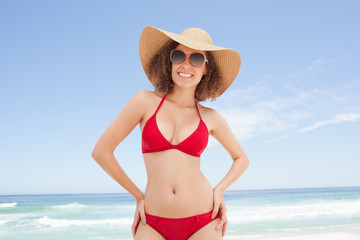 Woman in beachwear smiling with her hands on her hips