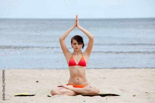 Young woman is sitting in joga position.