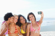 Woman holding a camera as she poses for a photo with her friends