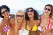 Four friends laughing while wearing sunglasses