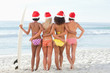 Four friends holding each other as they stand with a surfboard and Santa hats