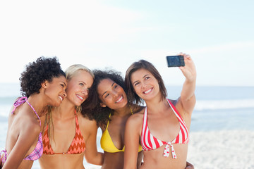 Four friends posing for a photo on the beach