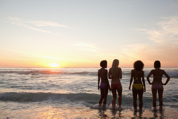 Four friends watching the sunset while standing near the waves