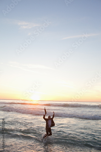 Businessman jumping in the waves