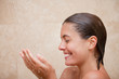 Side view of smiling woman enjoying a shower