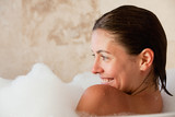 Smiling woman sitting in the tub
