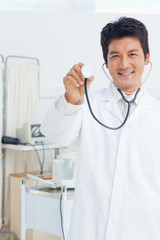 Doctor holding a stethoscope chestpiece in front of him