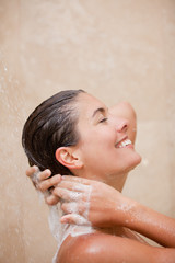Side view of smiling woman washing her hair in the shower