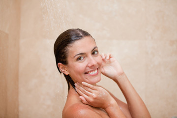 Side view of smiling woman taking a shower