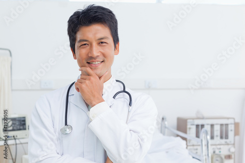 Doctor smiling as he holds his chin with his hand