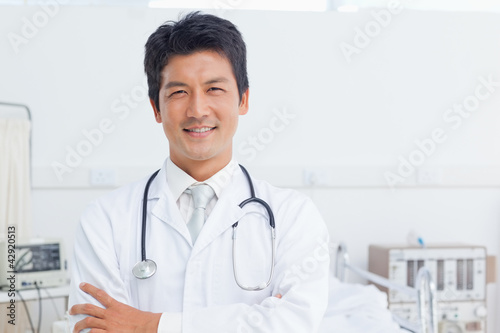 Doctor looking ahead with his arms folded