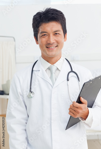 Doctor smiling while holding a black clipboard