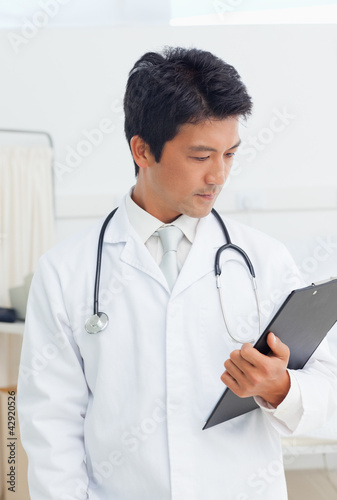Doctor looking at a clipboard