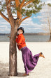 Happy Woman standing by the tree on a coast