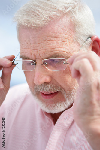 Senior man removing his glasses