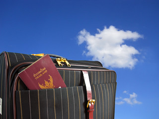 suitcase and thai passport isolated on a sky background