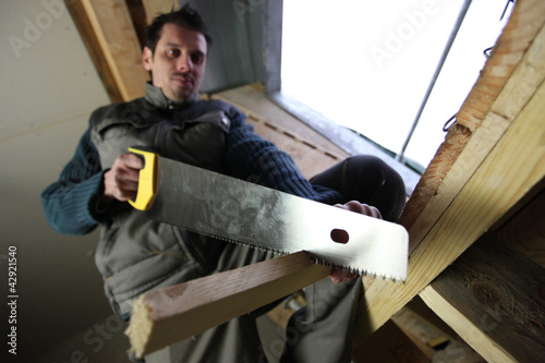 Carpenter using handsaw