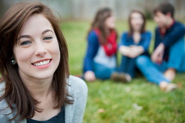 Smiling young girl with friends in the background