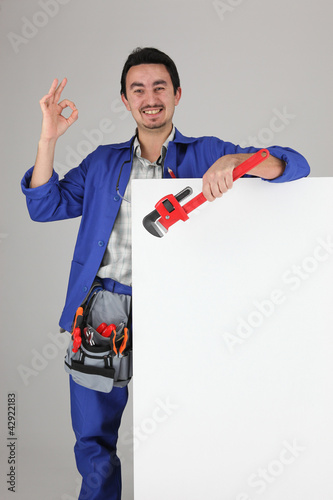 Tradesman giving the a-ok sign and standing behind a blank sign