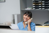 Nurse smiling while phoning and holding paper